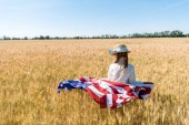 "Постер, картина, фотообои ""back view of kid in straw hat holding american flag in golden field in summertime """