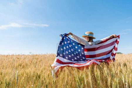 back view of kid in straw hat holding american flag in golden field