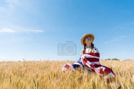 smiling kid in straw hat holding american flag in golden field with wheat