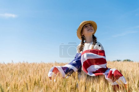 smiling child in straw hat holding american flag in golden field with wheat