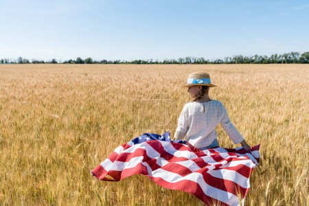 Photo for Cute child in straw hat holding american flag in golden field with wheat - Royalty Free Image