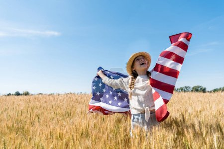 Photo for Cheerful child in straw hat holding american flag in golden field with wheat - Royalty Free Image
