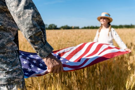 Photo for Cropped view of man in military uniform holding american flag with daughter in field - Royalty Free Image