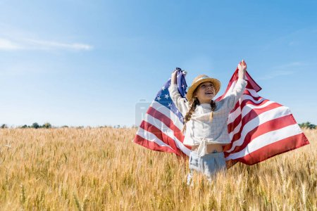 Photo for Cheerful child in straw hat holding american flag in golden field - Royalty Free Image