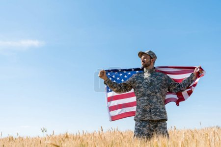 Photo for Soldier in cap and uniform holding american flag in field - Royalty Free Image