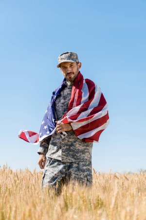 Photo for Selective focus of handsome soldier in cap and uniform holding american flag in field - Royalty Free Image