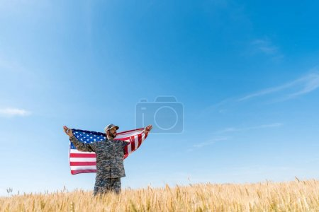 Photo for Soldier in cap and uniform holding american flag in field with wheat - Royalty Free Image