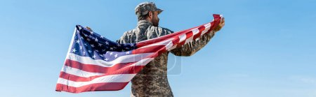 panoramic shot of soldier in cap and uniform holding american flag against blue sky