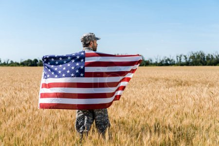 Photo for Soldier in cap and uniform holding american flag in golden field - Royalty Free Image