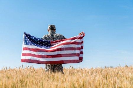 Photo pour Vue arrière de l'homme dans le chapeau et l'uniforme militaire retenant le drapeau américain dans le domaine - image libre de droit