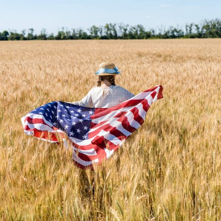 back view of child in straw hat holding american flag in golden field
