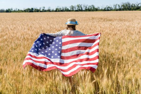 Photo pour Vue arrière de l'enfant dans le chapeau de paille retenant le drapeau américain dans le domaine d'or - image libre de droit