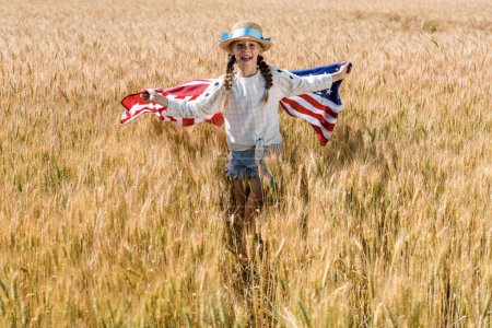 Photo for Happy kid in straw hat holding american flag in golden field - Royalty Free Image