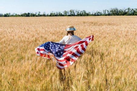 Foto de Vista trasera del niño sosteniendo bandera americana con estrellas y rayas en el campo de oro - Imagen libre de derechos