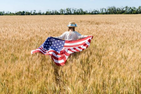 Photo for Back view of child in straw hat holding american flag with stars and stripes in golden field - Royalty Free Image