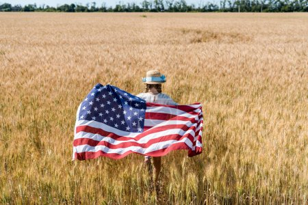 Photo for Back view of kid in straw hat holding american flag with stars and stripes in golden field - Royalty Free Image