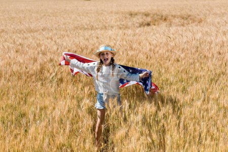 Photo for Cute and happy kid holding american flag in golden field - Royalty Free Image