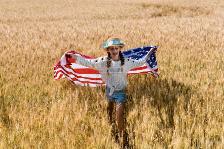 lindo y feliz niño sosteniendo bandera americana en el campo de oro