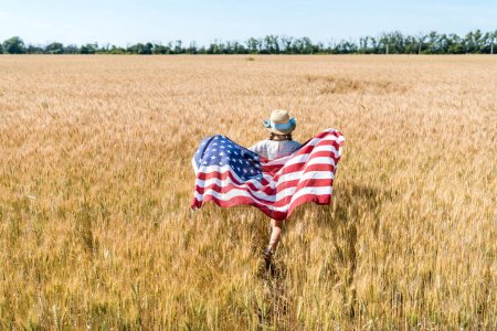 Photo for Back view of kid in straw hat holding american flag with stars and stripes in field with rye - Royalty Free Image