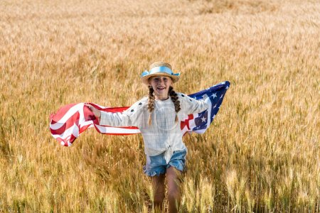 cute and happy kid holding american flag with stars and stripes in golden field