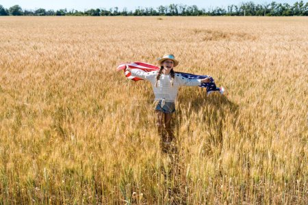 cute and cheerful kid holding american flag with stars and stripes in golden field
