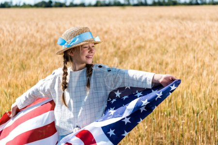 Photo for Cheerful kid holding american flag with stars and stripes in golden field - Royalty Free Image