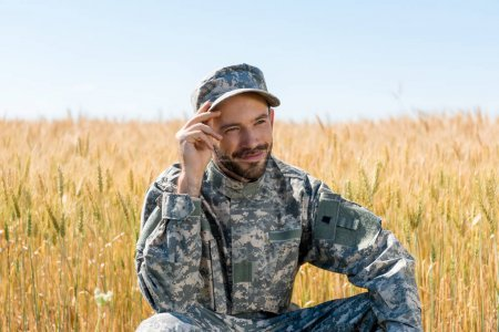 Photo for Positive military man touching cap and smiling in field - Royalty Free Image