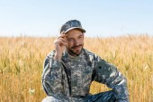 "Постер, картина, фотообои ""positive military man touching cap and smiling in field """