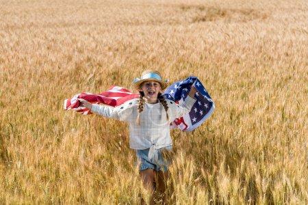 Foto de Alegre niño sosteniendo bandera americana con estrellas y rayas en el campo de oro - Imagen libre de derechos