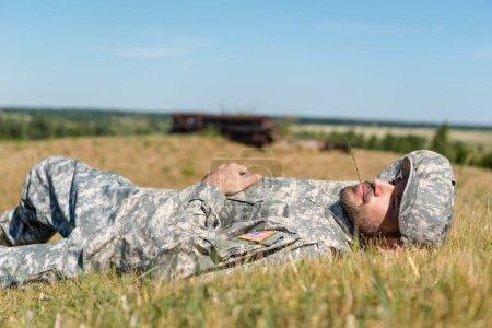 Foto de Soldado alegre con uniforme militar acostado en la hierba - Imagen libre de derechos