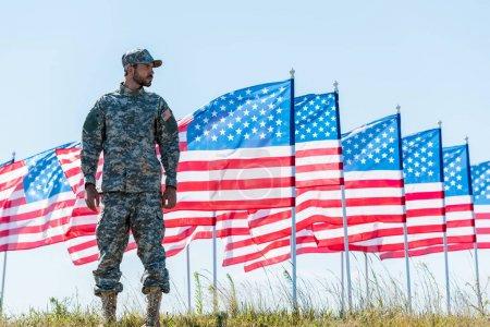 Photo pour Soldat patriotique dans l'uniforme restant près des drapeaux américains et du ciel bleu - image libre de droit