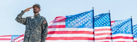 panoramic shot of patriotic soldier in military uniform giving salute near american flags with stars and stripes