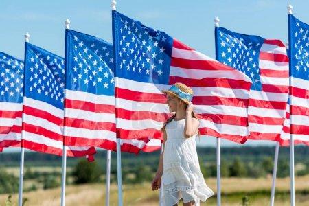Foto de Lindo niño patriótico de pie en vestido blanco cerca de las banderas americanas - Imagen libre de derechos
