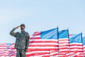 "Постер, картина, фотообои ""patriotic soldier in military uniform giving salute near american flags with stars and stripes """