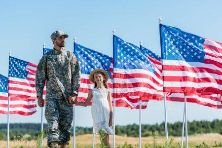 Photo pour Beau soldat tenant la main avec mignon enfant près des drapeaux américains - image libre de droit