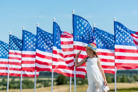 Photo for Happy patriotic child standing in white dress near american flags and waving hand - Royalty Free Image