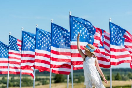 Photo for Cheerful patriotic child standing in white dress near american flags and waving hand - Royalty Free Image