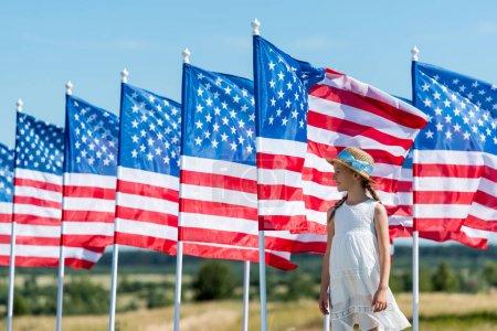 Photo pour Enfant gai debout en robe blanche et chapeau de paille près des drapeaux américains - image libre de droit