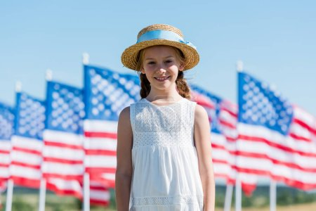 Photo pour Enfant heureux debout en robe et chapeau de paille près des drapeaux américains - image libre de droit