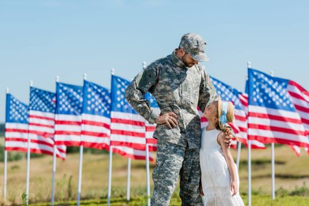 Photo pour Homme militaire dans le chapeau regardant l'enfant dans le chapeau de paille près des drapeaux américains avec des étoiles et des rayures - image libre de droit