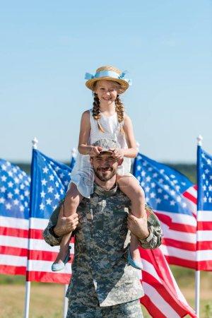 Photo pour Bel homme tenant sur les épaules fille heureuse en chapeau de paille près des drapeaux américains - image libre de droit