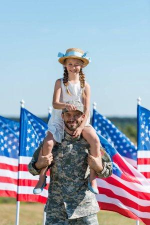 Photo pour Bel homme tenant sur les épaules joyeuse fille en chapeau de paille près des drapeaux américains - image libre de droit