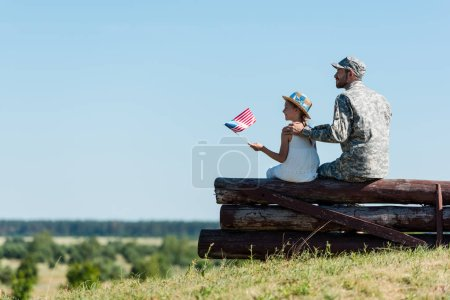 Photo for Cute child holding american flag near father in military uniform while sitting in fence - Royalty Free Image