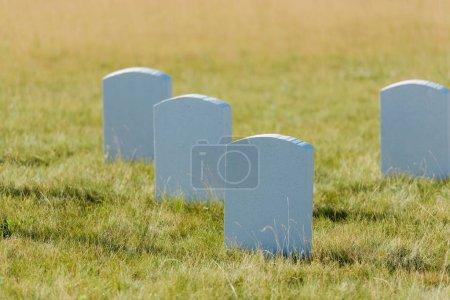 Photo pour Mise au point sélective des pierres tombales sur l'herbe verte et le ciel bleu dans le cimetière - image libre de droit
