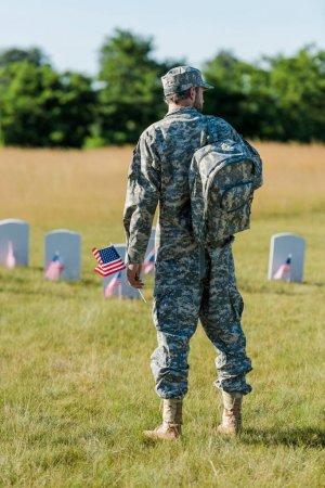 Photo pour Homme militaire retenant le drapeau américain près des pierres tombales dans le cimetière - image libre de droit