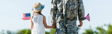 Photo for Panoramic shot of patriotic child and man in military uniform holding hands and american flags - Royalty Free Image