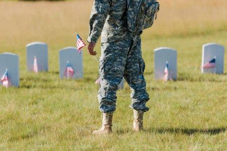 Foto de Vista recortada del hombre militar que sostiene la bandera americana cerca de lápidas en el cementerio - Imagen libre de derechos