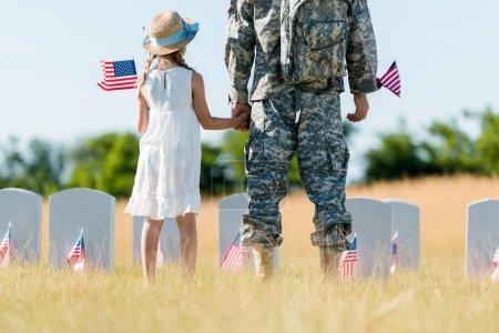 Photo pour Vue recadrée de l'homme militaire et de l'enfant patriotique tenant la main et des drapeaux américains - image libre de droit