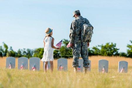 Foto de Niño en sombrero de paja y el hombre con uniforme militar de pie cerca de lápidas y la celebración de banderas americanas en el cementerio - Imagen libre de derechos