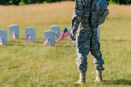 Foto de Vista recortada de soldado sosteniendo la bandera americana cerca de lápidas en el cementerio - Imagen libre de derechos